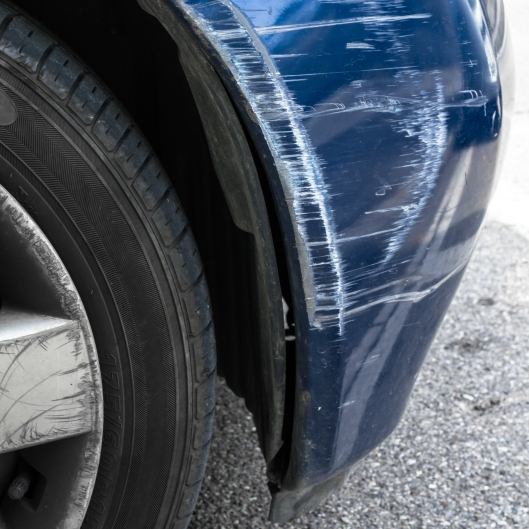 Accident damage to the front side of a blue car.